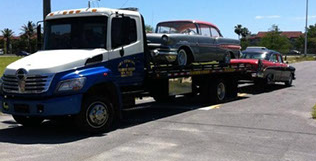 J&S towing truck providing antique towing services to two vehicles