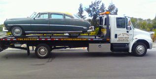 Green antique car on flatbed of J&S Towing and Transport tow truck